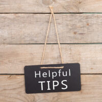 """Blackboards with inscription """"Helpful TIPS"""" on wooden background"""