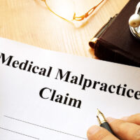 Medical Malpractice Claim on a table.