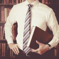 大きな本を持っているビジネスマン,本棚の背景