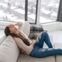 Headache and depression - winter blues anxiety woman feeling sick holding head and stomach in pain - menstrual period pain or tired.