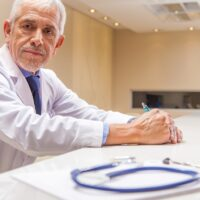 Worried expert male doctor expression with stethoscope in foregr